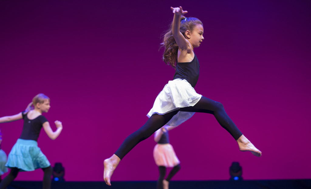 young contemporary dancer leaping across stage